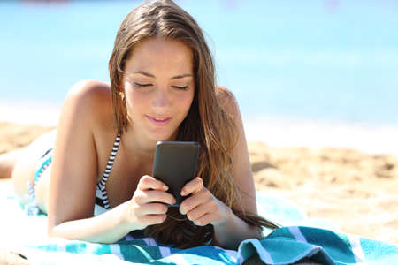 Relaxed girl in bikini sunbathing lying on a towel using smart phone on the beach on summer vacation