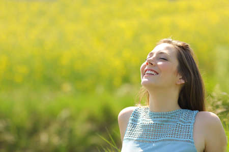 Happy woman resting breathing deep fresh air sitting in a yellow field