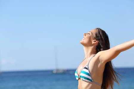 Side view portrait of happy woman in bikini breathing deep fresh air on the beach Фото со стока - 128721738