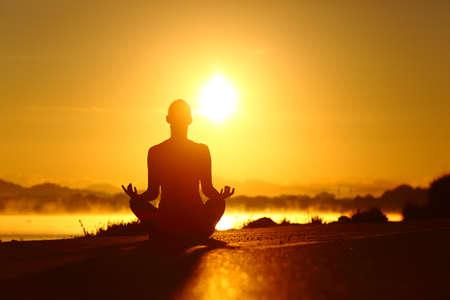 Rückansicht Porträt einer Frauensilhouette, die Yoga-Übungen bei Sonnenaufgang am Strand praktiziert