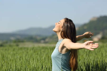 Side view portrait of a happy woman breathing deeply fresh air in a green field 스톡 콘텐츠