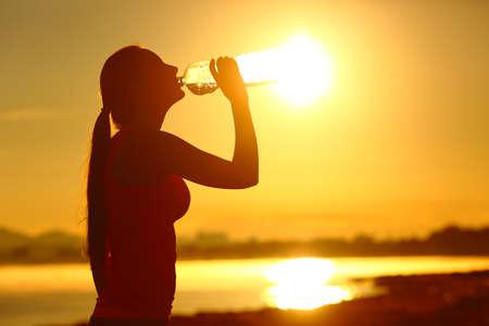 Silhouette de sportive buvant de l'eau en bouteille après le sport au coucher du soleil