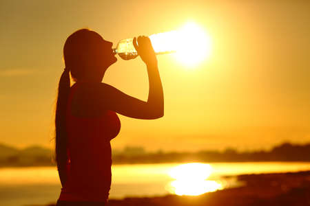 Sportswoman silhouette drinking bottled water after sport at sunset