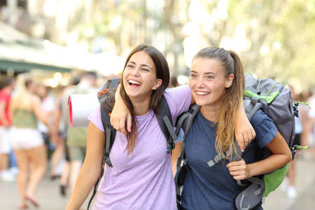 Front view portrait of two happy backpackers laughing enjoying vacation in a city street