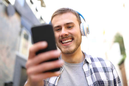 Portrait of a happy man listening to the music with smart phone walking in the street