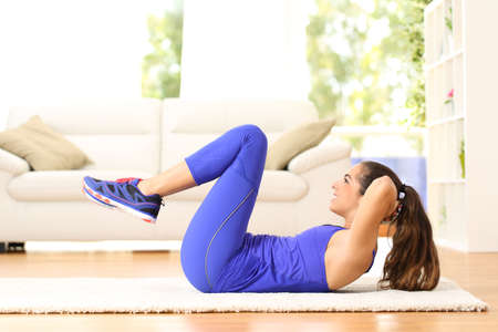 Side view portrait of a sportswoman exercising abs doing crunches at home