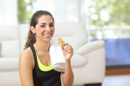 Happy woman holding an energy bar after sport sitting on the floor at home