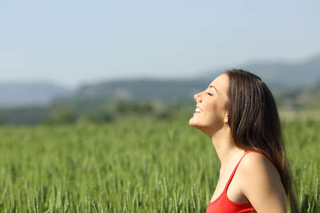 Happy woman in red breathing fresh air in a green field a sunny day Stockfoto