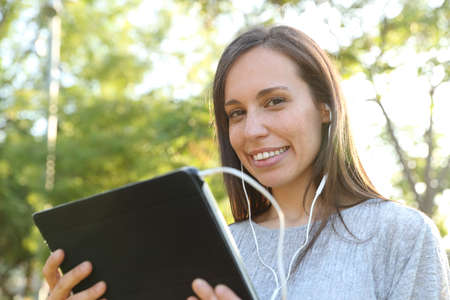 Happy adult woman wearing earphones and holding a tablet looks at you in a park