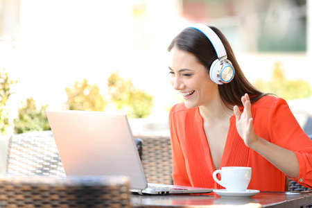 Happy woman having a video call with a laptop sitting in a coffee shop terrace Imagens