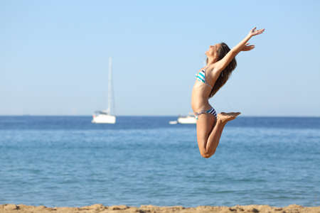 Side view portrait of an excited woman in bikini jumping on the beach celebrating summer vacation Фото со стока