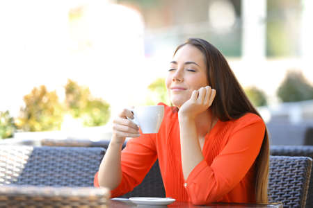 Relaxed woman enjoying breakfast smelling coffee sitting in a bar terrace