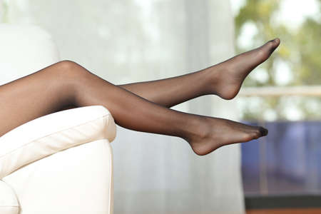 Side view of woman legs wearing nylons lying on a couch at home 스톡 콘텐츠