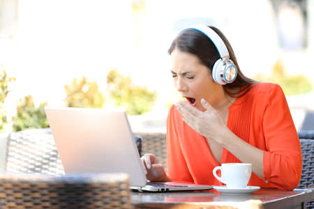 Tired woman in orange yawning using a laptop in a bar terrace