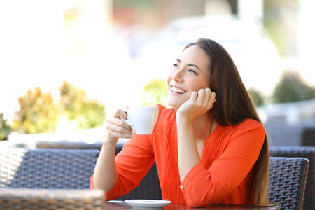 Happy woman thinking drinking coffee sitting in a resturant terrace 写真素材