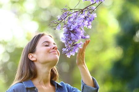 Candida donna che odora di fiori in piedi in un parco
