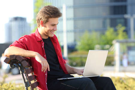 Happy man sitting on a bench using a laptop to watch online videos in a park