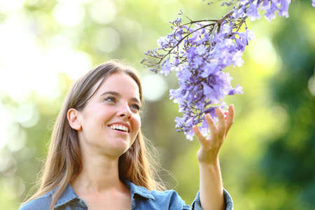 Happy woman enjoying nature touching flowers standing in a park Фото со стока - 128723325