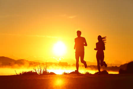 Back light portrait of a couple shilouette of runners running at sunrise on the beach Imagens