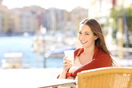 Happy woman looking at camera holding a drink in a coffee shop in a coast town Stok Fotoğraf