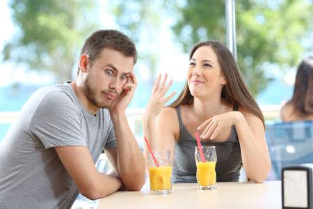 Gelangweilter Mann, der ihrer Freundin in einer Bar oder einem Hotel am Strand zuhört on