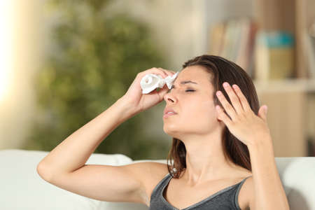 Girl sweating drying forehead and fanning at home in a warm day