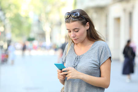 Portrait od a serious teen texting on smart phone standing in the street