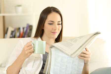 Relaxed woman at home reading a newspaper drinking coffee sitting on a couch in the morning