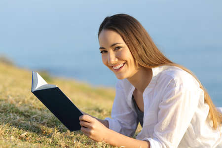 Happy reader holding a paper book lying on the grass looks at you