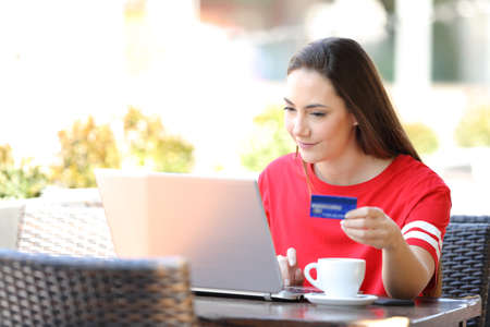 Serious girl paying online with a laptop and credit card sitting in a coffee shop terrace
