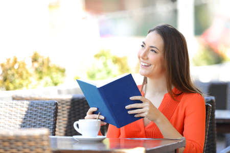 Happy woman reading a book dreaming looking away sitting in a coffee shop terrace