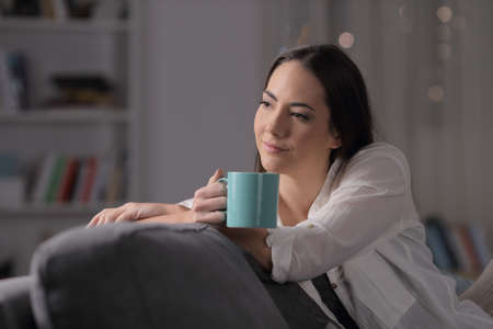 Pensive woman holds a mug and looks away sitting on a couch in the night at home Stockfoto