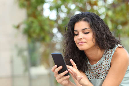 Relaxed woman is browsing smart phone content sitting in a park Stok Fotoğraf