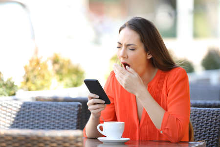 Tired woman yawning holding smart phone in a bar terrace