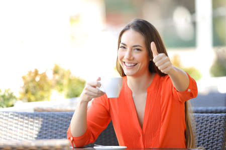 Happy woman with thumb up in a bar holding a coffee cup sitting in a restaurant terrace Stockfoto