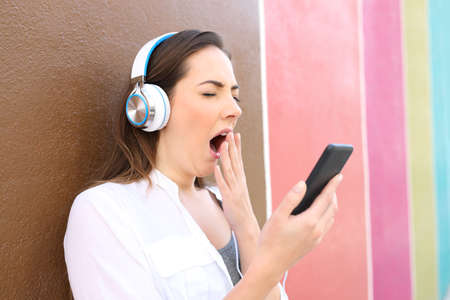 Bored woman yawning using smart phone and headphones to listen to music in a colorful street 写真素材
