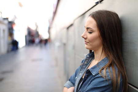 Side view portrait of a sad girl alone complaining leaning on a wall in a solitary street 写真素材