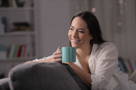 Pensive woman drinks coffee looking at side in the night sitting on a sofa in the living room at home