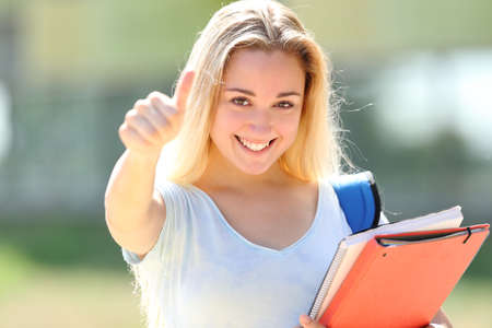 Happy student posing looking at camera with thumbs up in an university campus