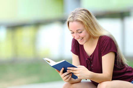 Happy student studying reading a paper book sitting outdoors in a campus