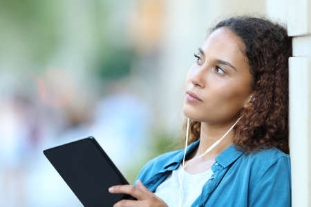 Serious mixed race woman thinking looking away listening to music with tablet and earphones in the street