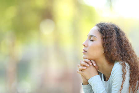 Side view portrait of a serious mixed race woman meditating and breathing fresh air outdoors in a park