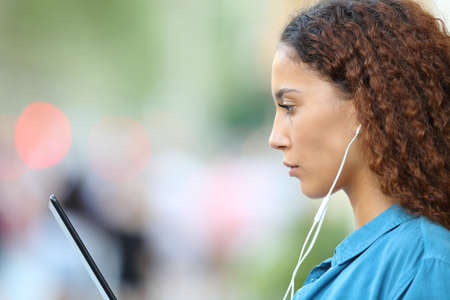 Side view portrait of a serious mixed race woman e-learning using tablet and earphones in the street Archivio Fotografico