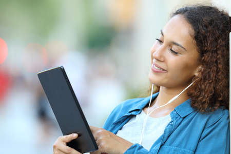 Happy mixed race woman listening music or watching media content with a tablet in the street