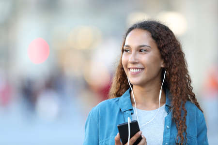 Front view portrait of a mixed race woman listening to music looking at side in the street 스톡 콘텐츠 - 129968499