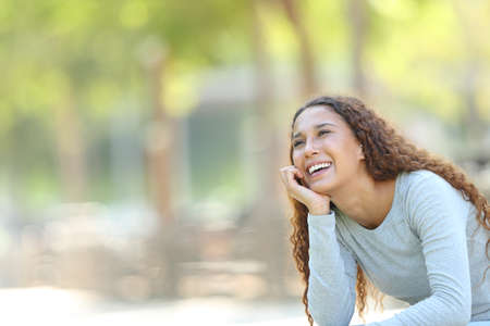 Happy mixed race woman dreaming looking at side sitting in a park with copy space