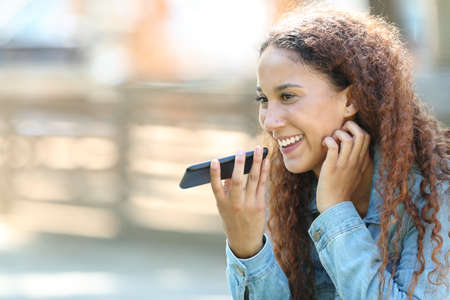 Gelukkig gemengd ras vrouw met behulp van spraakherkenning op smartphone om berichten op te nemen in een park Stockfoto