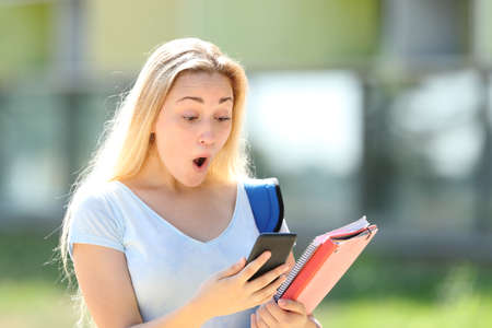 Amazed student checking smart phone content outdoors in an university campus Stockfoto