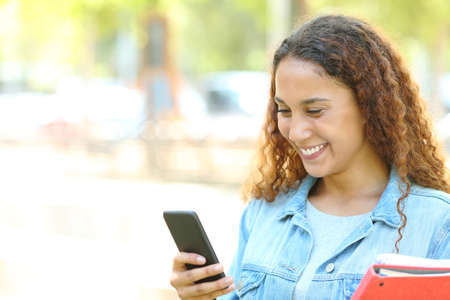 Happy mixed race student checking smart phone content in a park or campus