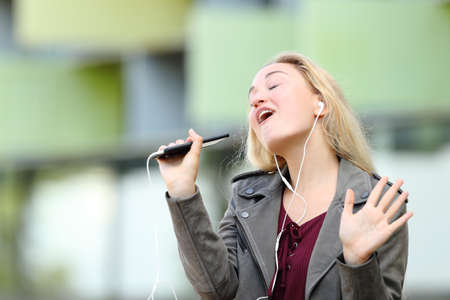 Happy teen singing karaoke using smart phone app and earbuds outdoors
